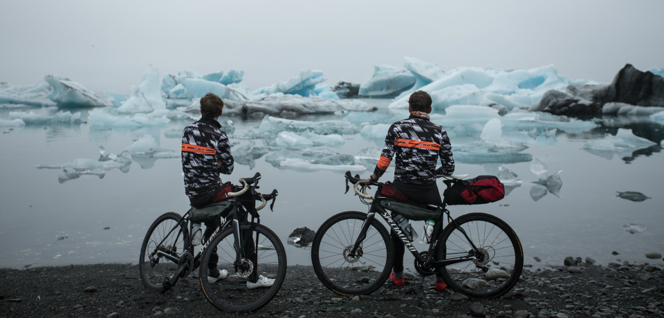 Cyclists looking at ice on a lake.