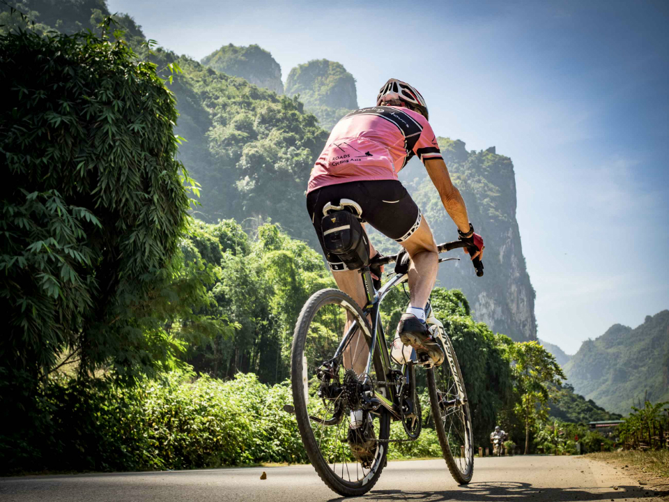 Cyclist riding on a road in Vietnam.