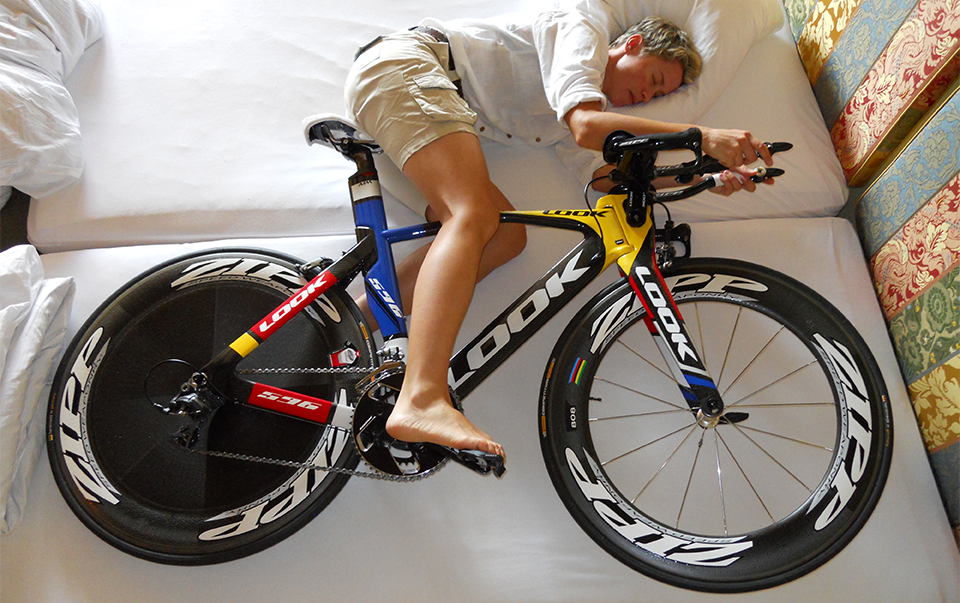 Cyclist sleeping on his bike in the bed
