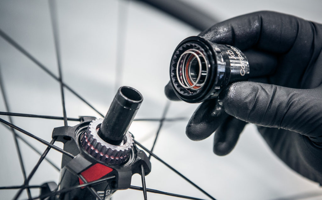 Cyclist changing part of his wheel.