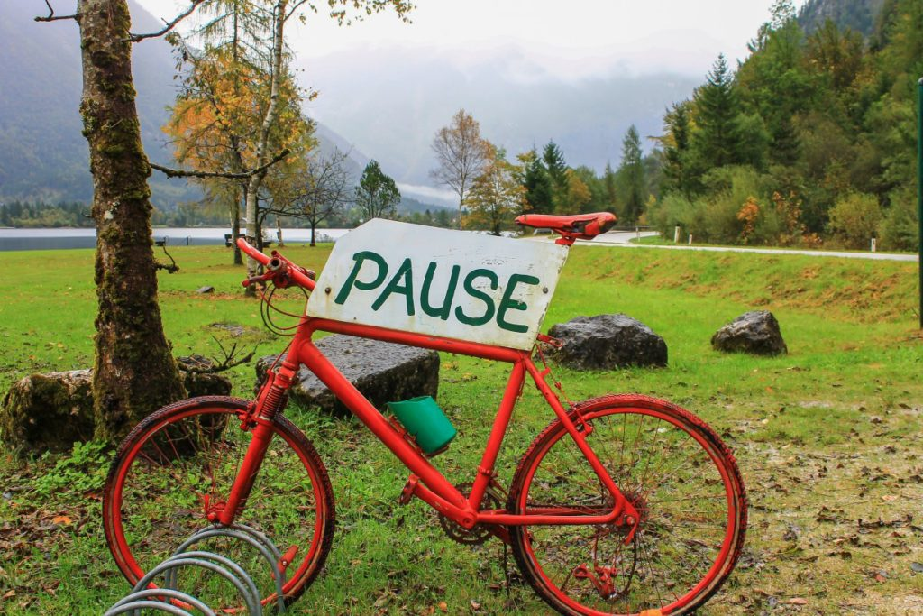 """Red bicycle with a """"pause"""" sign on it."""